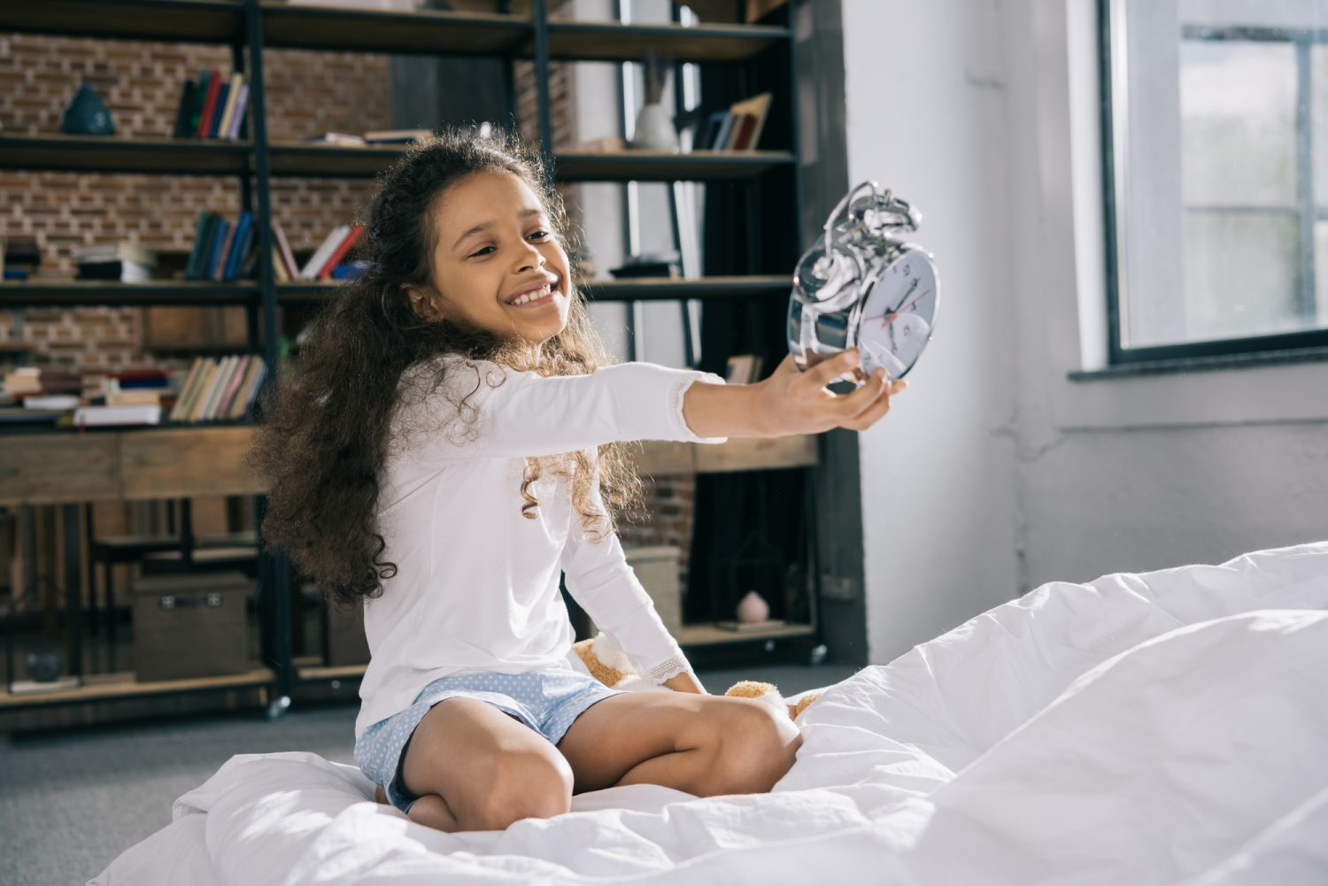 young girl holding alarm clock